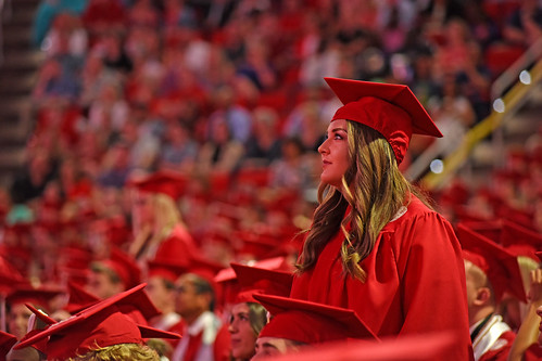 Student watches the Jumbotron as she stands with her college.