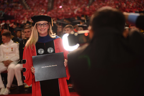 Graduate poses for a photo after accepting her degree.