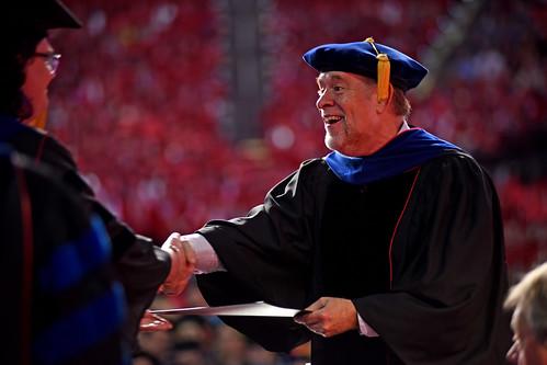 Graduate school dean Peter Harries congratulates a student.