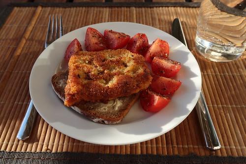 Schnitzel auf gebuttertem Roggenbrot mit aufgeschnittenen Tomaten