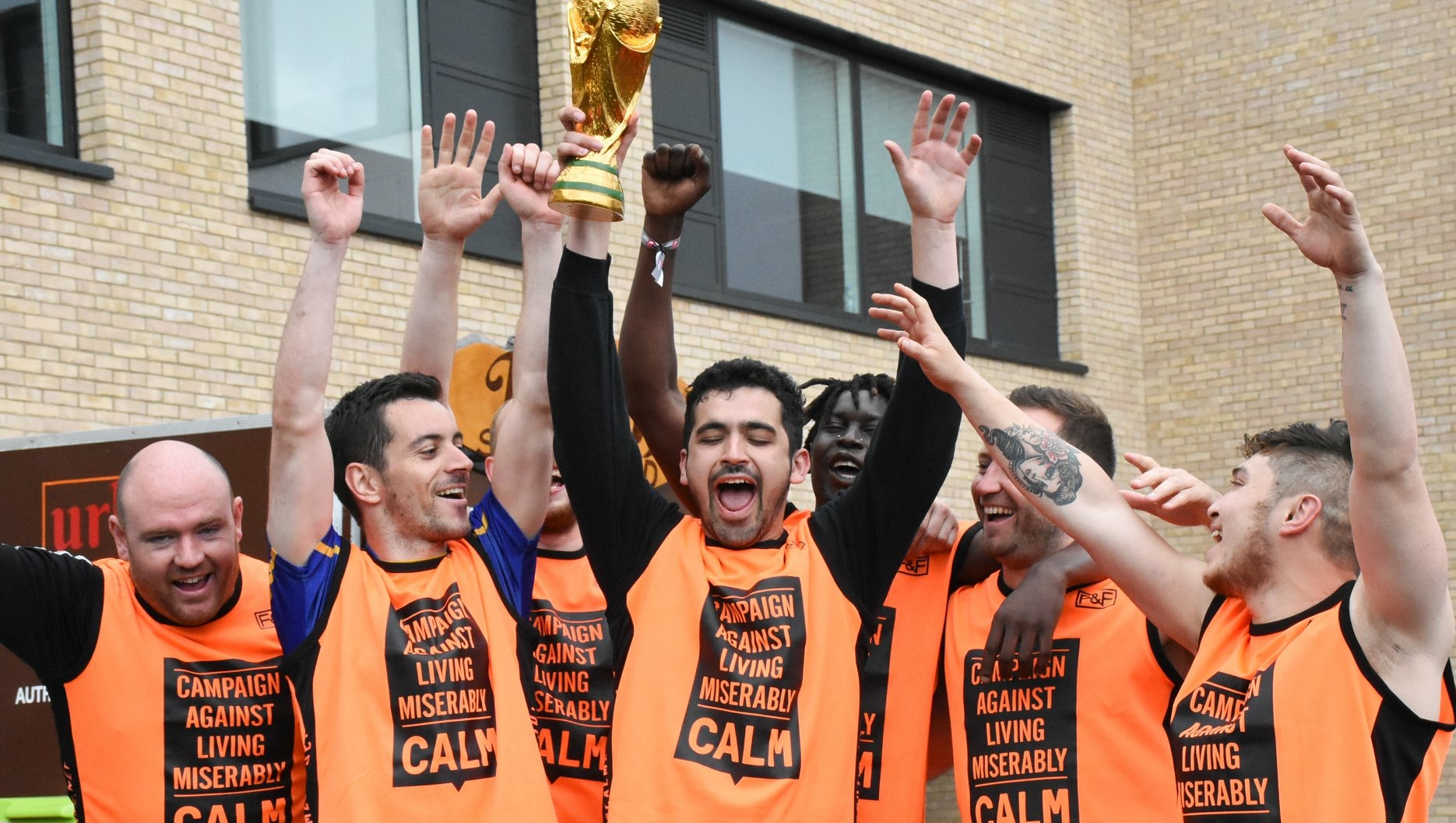 7 men lifting a trophy in celebration