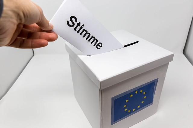 Männerhand bei der Stimmabgabe für die Wahl des Europäischen Parlaments, steckt den Stimmzettel in die Wahlurne