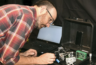 Aaron Anderson adjusts a field-portable version of the optical biosensor.
