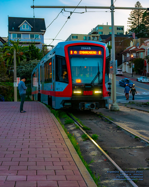 A MUNI PASSENGER WAITS FOR A LRV4 TO STOP FOR HIM