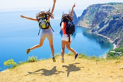 two young caucasian females jumping on a cliff above the sea