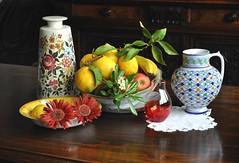 Due gerbere, frutta e vasi