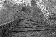 "A person ascends the higher middle part of an arched bridge, where its cornerstone is wedged.  This is the Kókkoris's or Noutsos's bridge, made of stones, in central Zagori, Greece. The protruding cobblestones' pavement is visible. Steep, gigantic rock cliffs surround the bridge with the entrance to a cave seen in the background.  This sort of extreme terrain along with the human presence —both as physically there and as indirect presence through the existence of a man-made structure— offers rich texture and shapes; the latter are best presented in black and white; a pictorially timeless, artistic look is also provided this way. So, colour information was deliberately discarded!  The arched bridge was built in 1750 and is located near the Kipoi (Kēpoe, Κῆποι) village. It is 23.6 m (77 ft) long, 13 m (43 ft) high and spans the Vikakēs or Voïdomátēs river. Kēpoe is one of the 46 Zagóri villages or Zagorochória. They are all built in high altitude, on Pindus range of mountains, in northwestern Greece. Zagori is an area of great natural beauty, with striking geology and two National Parks.  The ascending individual's photograph is reminiscent of the following poem lines:  ""We have not wings, we cannot soar;  But we have feet to scale and climb""  —Henry Wadsworth Longfellow (The Ladder of St. Augustine)"