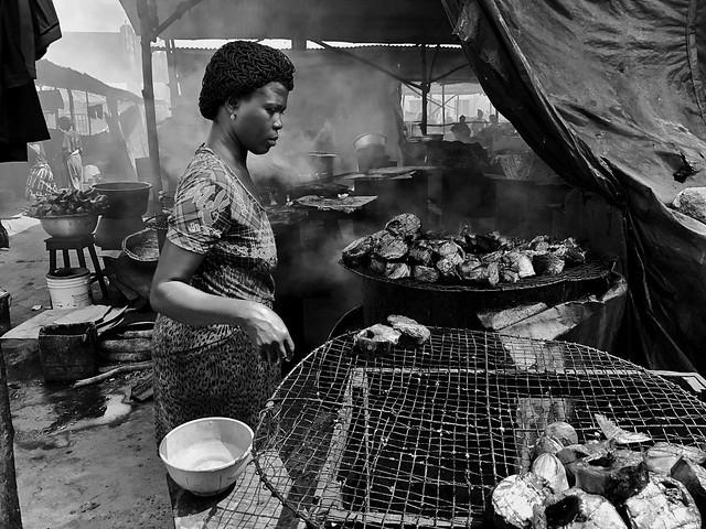 Fotografía en blanco y negro de una mujer ahumando pescado en un mercado de Cotonou (Benín)