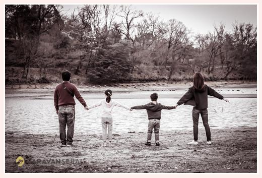 湖の前で手をつないで立つ家族の後ろ姿
