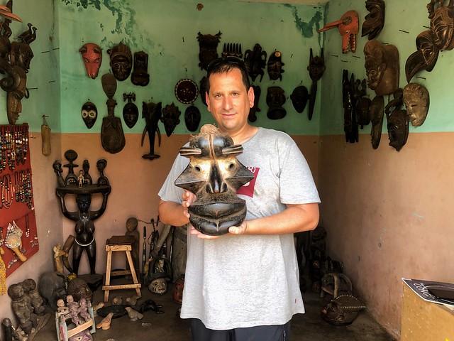 Sele en una tienda de arte africano en Benín sosteniendo una máscara