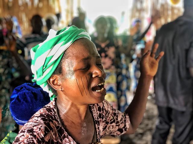 Mujer cantando en misa en Benín