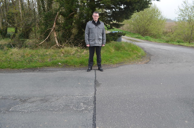 Archdeacon Robert Miller astride the border line with Northern Ireland at left and the Republic at right.
