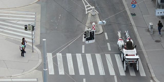 Eine weiße Kutsche, gezogen von zwei weißen Pferden, überquert einen Personen stehen am Straßenrand und beobachten dies.Zebrastreifen. Zwei
