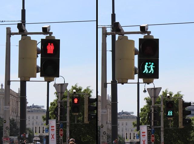 Das Bild zeigt zwei Fotos nebeneinander. Das linke Foto zeigt eine rote Fußgängerampel. Auf dem Ampelsymbol umarmen sich zwei stehende Männchen. Das rechte Foto zeigt eine grüne Fußgängerampel. Auf dem Ampelsymbol gehen zwei Ampelmännchen Hand in Hand, zwischen ihnen ein Herzchen.