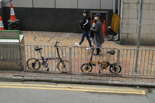 Folding bikes chained up to a roadside fence