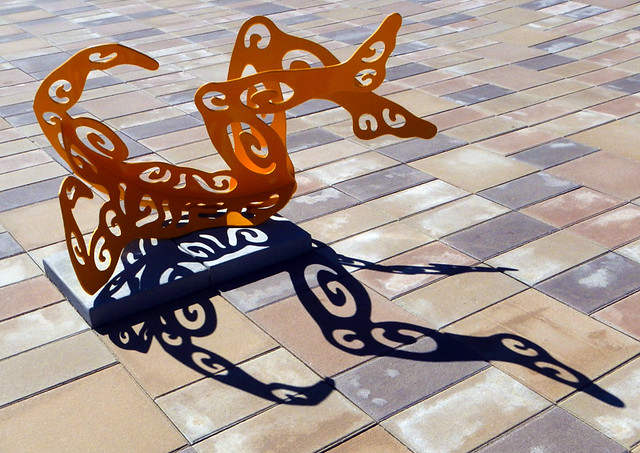 Sculpture and shadows of a yellow man pierced with native designs in an Art Gallery on a Washington state drive