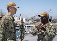 Rear Adm. Cedric Pringle applauds Religious Program Specialist Seaman David Miller during an awards ceremony for his efforts in apprehending a woman threatening a church congregation on April 20, 2019. (U.S. Navy/MCSN Cosmo Walrath)