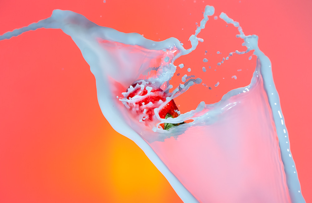 Food Photography. Milk Droplets Pouring Around Strawberry. Against Red Background.