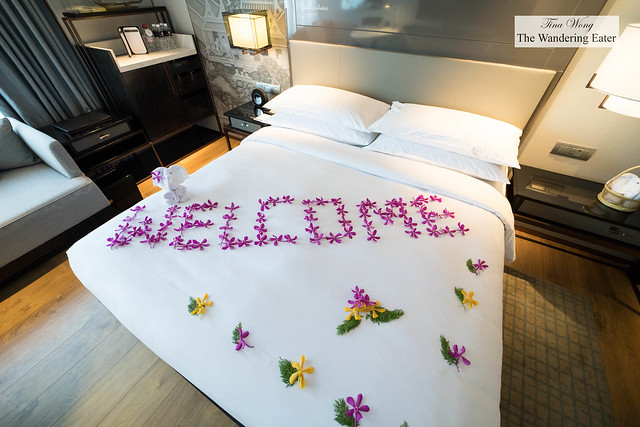 King sized bed with 'welcome' written with fresh flowers