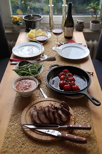 Lammkeule in Tomatensoße, mit heißen Tomaten, Prinzessböhnchen und Salzkartoffeln (Tischbild)
