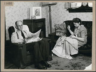 J.W. (Ed) Maddocks reading a newspaper in his living room while his wife sews, Toronto, Ontario / J.W. (Ed) Maddocks lit un journal dans son salon pendant que son épouse coud, Toronto (Ontario)