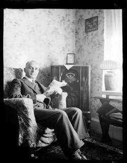 Mr. Tatarian sitting on a living room chair holding a magazine / M. Tatarian assis dans son salon, tenant un magazine