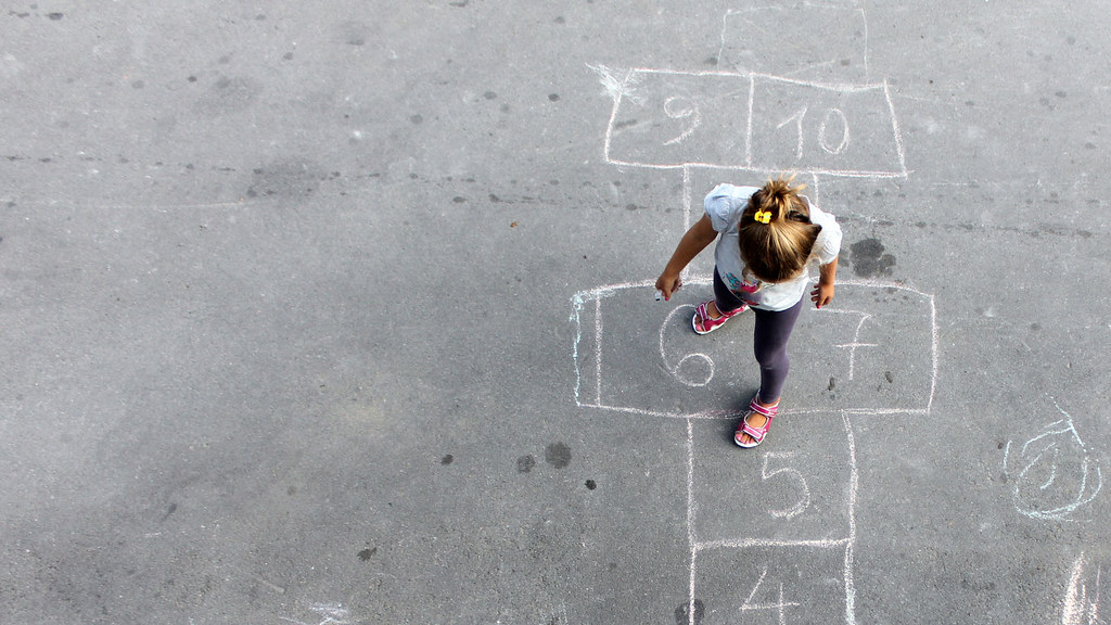 A photo of a girl in a playground playing hopscotch