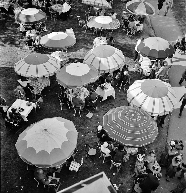 At the Races: Pimlico racetrack, near Baltimore, Maryland. Outdoor diner sitting under beach umbrellas, May 1943.