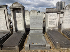 A row of graves in a cemetery, with a tower block visible behind.