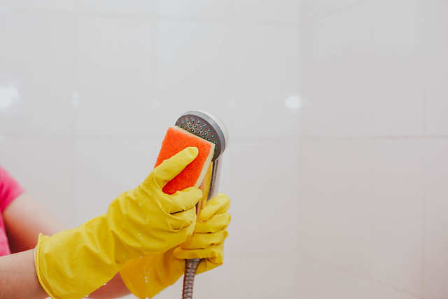 Woman in yellow gloves cleaning showers head