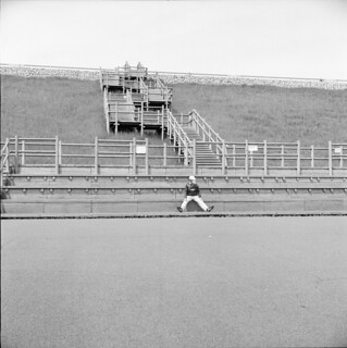 A man who sits on the foot of an embankment.