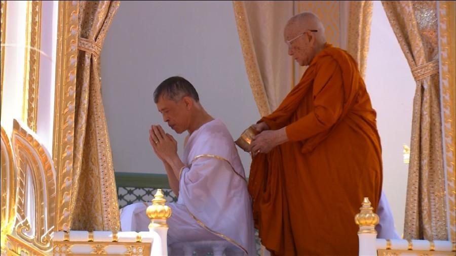 Sangharaja Thailand menuangkan air pada tubuh Raja Vajiralongkorn dalam upacara abhiseka pada Sabtu (4/5/2019) di kompleks Istana Kerajaan.