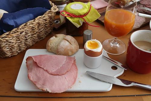 Backschinken auf frisch gebackenem Brötchen zum Frühstücksei