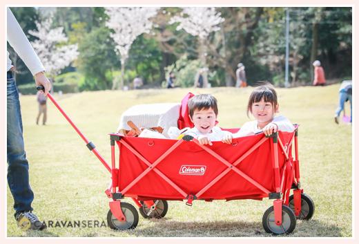 赤いキャリーカートに乗る子供 公園