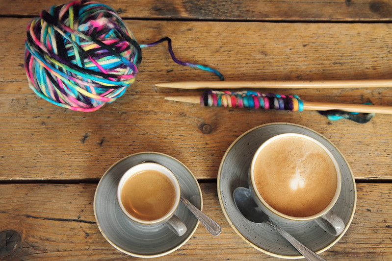 Coffee cups and knitting on a wooden table