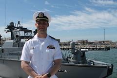 Lt. Andrew Bergstrom poses in front of a Mk VI patrol boat after assuming command of Coastal Riverine Squadron Three Alpha Company Crew Two, April 18.  (U.S. Navy/Lt. Kara Handley)