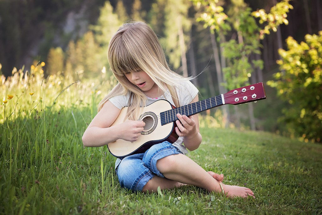 A Little Girl Playing Guitar Outdoors