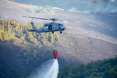 An MH-60S Sea Hawk from Helicopter Sea Combat Squadron (HSC) 25 drops water on a fire on Guam, May 9. (U.S. Navy/JoAnna Delfin)