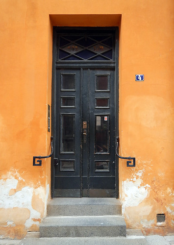 Black door set into an orange wall wall in Copenhagen, Denmark