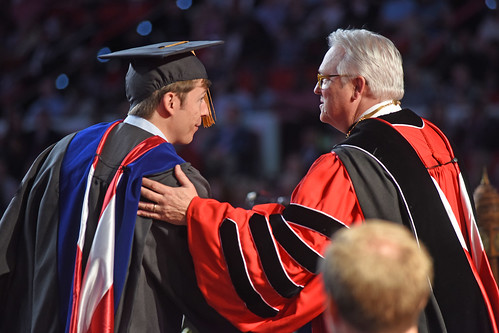 Chancellor Randy Woodson (right) congratulates a new graduate school graduate.