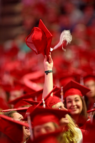 Student waves her mortar board to let her family know where she's sitting for commencement.