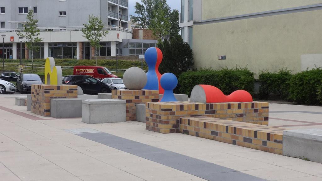 1987 Berlin-O. Spielfiguren mit Sitzlandschaft in Pop Art von Hans Ticha Alkydharz/Beton Franz-Stenzer-Straße 39 im Quartier Marzahner Promenade in 12679 Marzahn