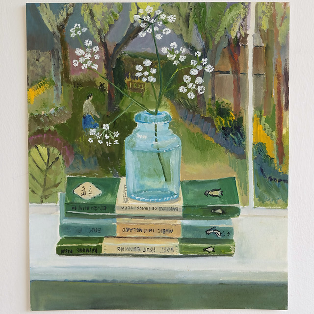 a wild sprig in a bottle with books, garden view