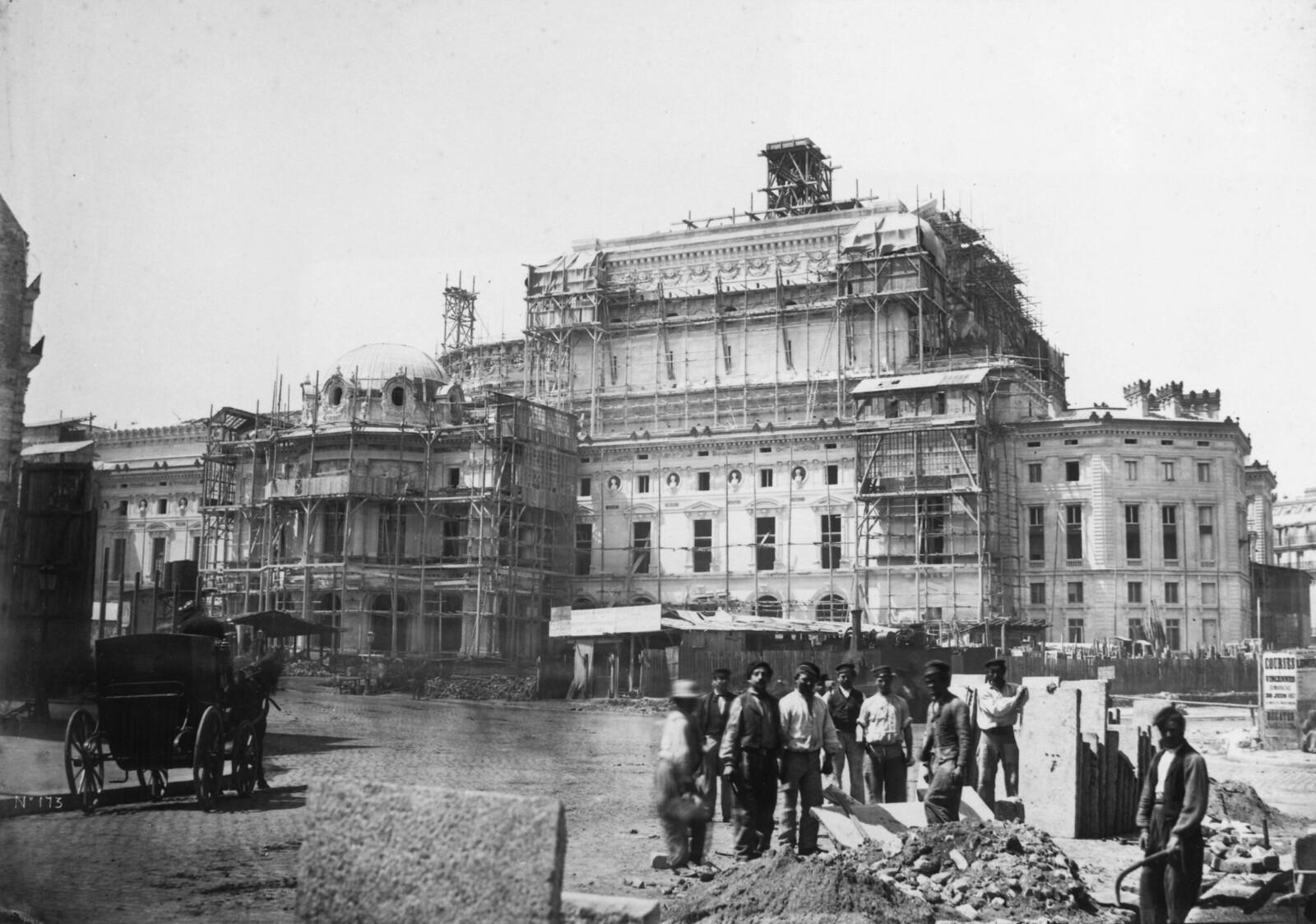 1870.  Группа из девяти рабочих стоит с плитами перед почти завершенным оперным театром, который покрыт лесами
