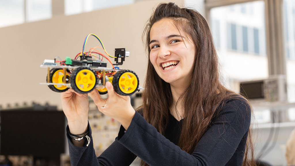 Maria smiles as she holds up her Arduino robot
