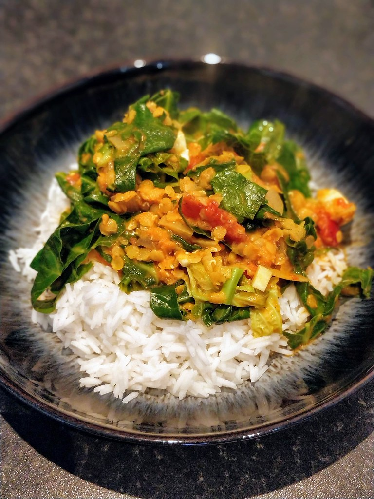 Spring greens, halloumi and red lentil curry in bowl with rice