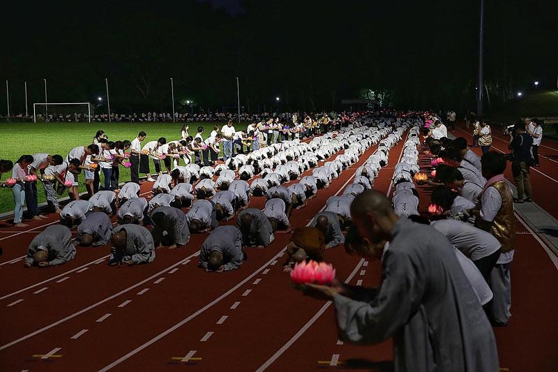 """Umat Buddhis Singapura melakukan """"San By Yi Bai"""" di Stadion Bukit Gombak, Singapura, pada malam Vesak,"""