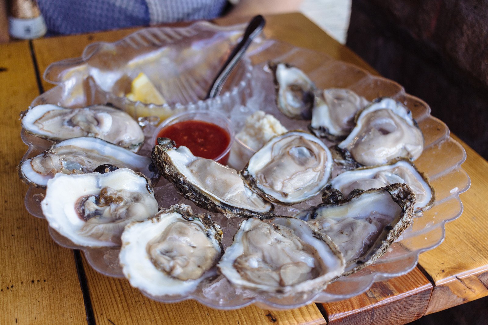 A platter of shucked oysters on the half shell over ice with containers of cocktail sauce and horseradish