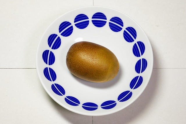 Kiwifruit_(2019_05_19)_1_resized_1 青色の模様が描かれた白色の丸い皿に乗った1個のキウィフルーツを斜め上から撮影した写真。