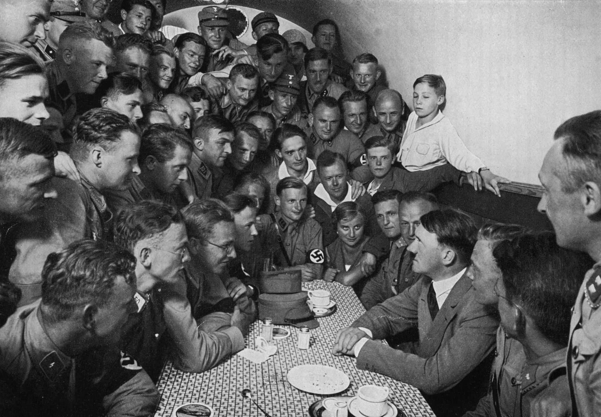 1935. Адольф Гитлер сидит за столом перед группой молодых национал-социалистов в маленькой комнате в «Коричневом доме» (штаб-квартира НСДАП), Мюнхен